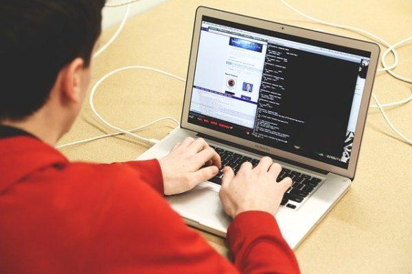 赤い服の人がパソコンでコーディングを行なっている