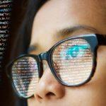 プログラミングコードを見つめる眼鏡をかけた女性