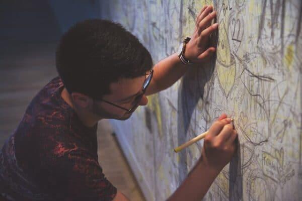 壁に鉛筆で絵を描く男性